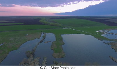Aerial view river mouth flowing to wilderness lake low level...