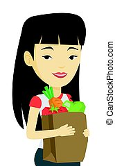 Happy woman holding grocery shopping bag.