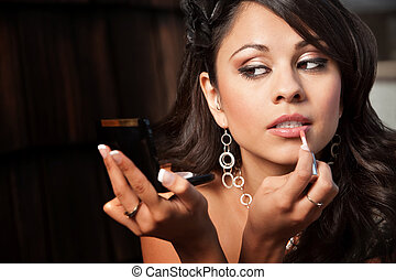 Beautiful Latina Woman with Compact Applying Lip Gloss -...