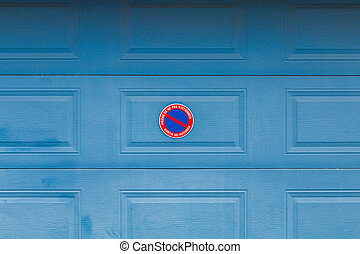 """Garage door with panel in French """"Please do not park Car exit"""""""