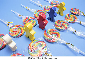 Lollipops with Wooden Figures on Blue Background