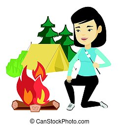 Woman roasting marshmallow over campfire. - Asian woman...