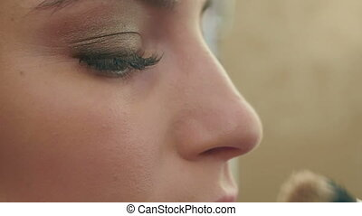 Professional makeup, application of powder on the noce....
