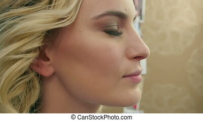 Side view of blush being applied on cheekbones of beautiful...