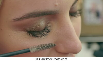Combing women new long black eyelashes. Close up. Slow...