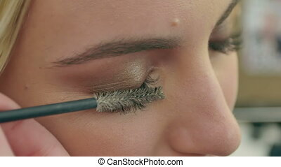 Professional make-up artist combing eyelashes of model....