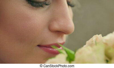 Young women smelling on roses and smiling. Close up. Slow...