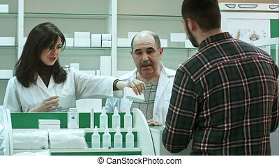 Attractive woman and senior pharmacist listening to male customer dissapointed of medicine quality and try to solve the problem