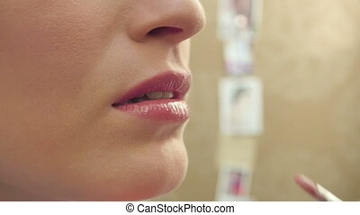 Makeup artist finishing apply lip gloss and young model...