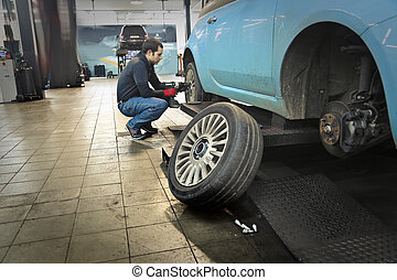Car being repaired by mechanican