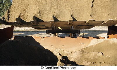 Wheel loader unloads sand in the bunker at the plant during...