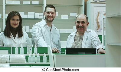 Portrait of a pharmaceutical team smiling and looking at...