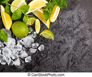 Lime, lemon, mint and crushed ice on a black background. The...