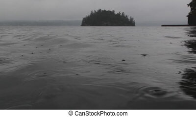 Lake surface in the rain. - Rain falling on surface of...