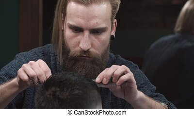 Male barber cutting hair of man in Barbershop