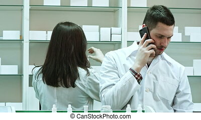 Female and male pharmacists working in pharmacy, talking via...
