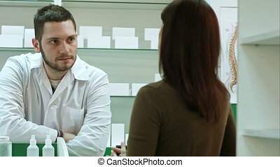 Male pharmacist and female client at pharmacy. Professional...