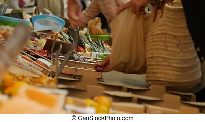 Girl picking out fresh produce at a market.