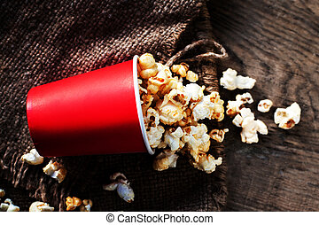 Fresh Popcorn in a red cardboard box on the wooden table,...