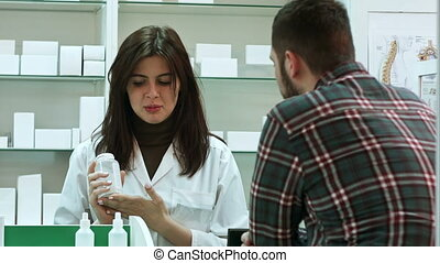Young female pharmacist suggesting medical drug to male...