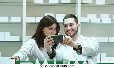 Smiling two pharmacist taking selfie in pharmacy. Close up....