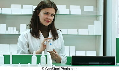 A cheerful young woman pharmacist with a bottle of drugs...