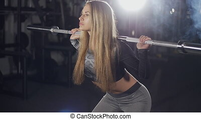 Fitness woman doing barbell squats in a gym - Young fitness...