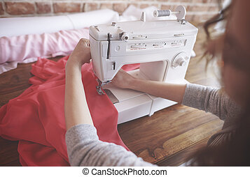 Back view of intent seamstress sewing