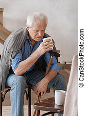 Cheerless aged man holding a cup - Empty chair. Cheerless...