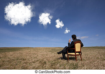 Thinking about the future - businessman sitting in a chair...
