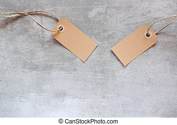Gift tags made from recycled paper with string on concrete...