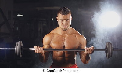 Man doing weight lifting in gym on black background.