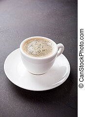White cup of coffee on dark brown background with copy...
