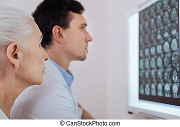 Serious elderly woman visiting an oncologist