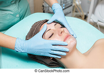 anti-aging facial massage. cosmetologist doing massage for...