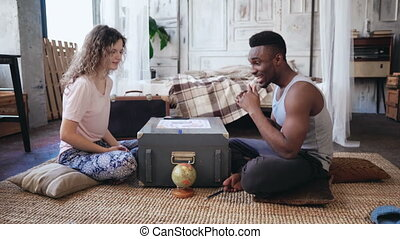 Multiracial couple in pajamas sitting on the floor and...