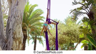 Graceful female acrobatic dancer hanging suspended from two...