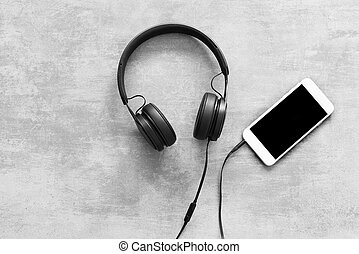 Headset and a phone on concrete background - Headset and a...