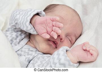 Cute newborn baby sleeping, focus on hand