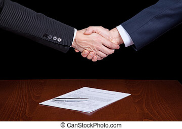 Closing the contract - handshake between two businessman...
