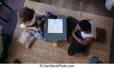 Top view of multiracial couple sitting on floor and playing...