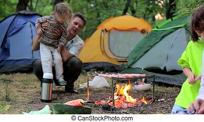 Bonfire night in a tent camp in the countryside. - Man,...