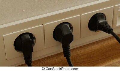 Close up of man hand putting plug in electricity socket.