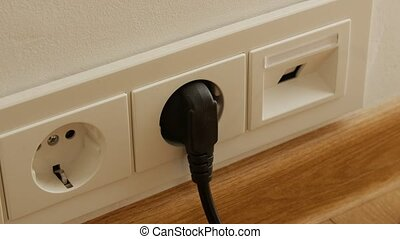 Close up of man hand putting plug off electricity socket.