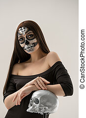 Woman with smart artistic makeup in horror style posing with...