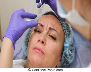 Rejuvenating facial injections. - Middle-aged woman on...