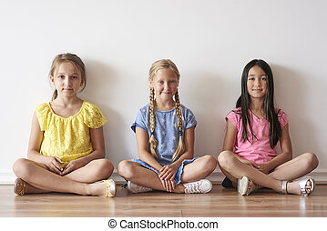 Three girls sitting with crossed legs