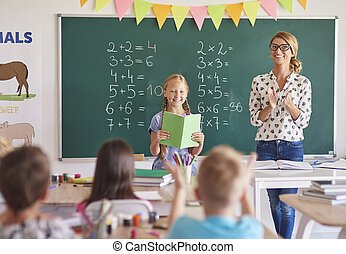 Girl student with clapping teacher