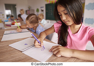 Dark hair girl drawing in the classroom
