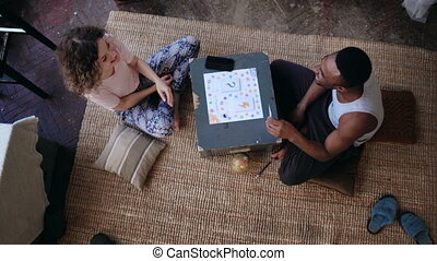 Multiethnic couple in pajamas sitting on the floor and...